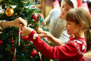 Young Girl Places a Red Ornament on the Christmas Tree